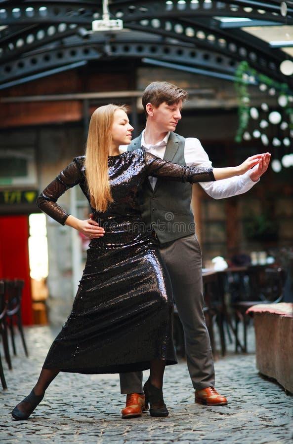 Χαρούμενα νέα ερωτευμένα χορεύοντας λατινικά ζευγών στην οδό βραδιού κοντά στον καφέ της παλαιάς πόλης στοκ φωτογραφίες με δικαίωμα ελεύθερης χρήσης