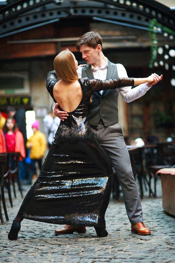 Χαρούμενα νέα ερωτευμένα χορεύοντας λατινικά ζευγών στην οδό βραδιού κοντά στον καφέ της παλαιάς πόλης στοκ φωτογραφία με δικαίωμα ελεύθερης χρήσης