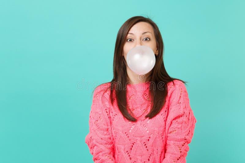 Χαρωπή νέα γυναίκα στο πλεκτό ρόδινο πουλόβερ μπαλόνι γόμμας φυσαλίδων μασήματος φυσώντας που απομονώνεται στο μπλε τυρκουάζ υπόβ στοκ εικόνες με δικαίωμα ελεύθερης χρήσης