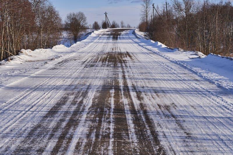 Χειμερινός δρόμος με την άσφαλτο, που καλύπτεται μερικώς με το χιόνι στοκ εικόνα