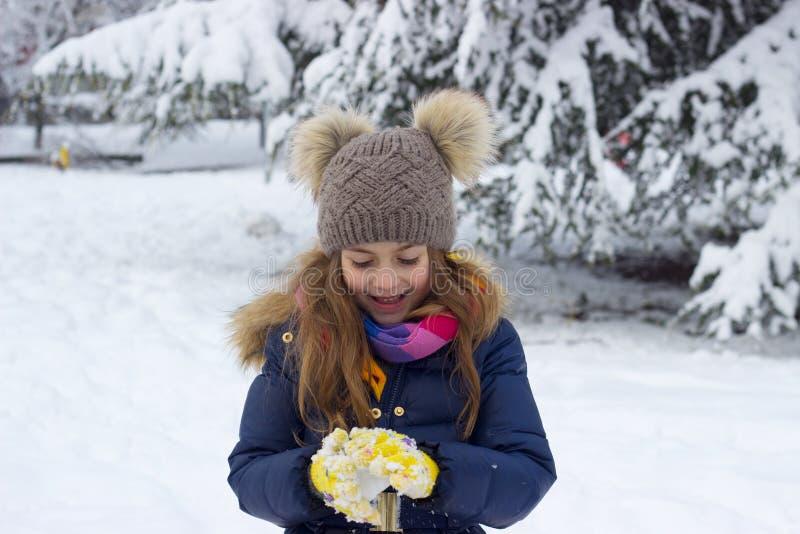 Χειμερινό πορτρέτο ενός χαμογελώντας όμορφου μικρού κοριτσιού στο χιόνι στοκ εικόνα