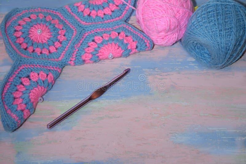 Χειροποίητη πλεκτή ρόδινος-μπλε κάλτσα με τα νηματοδέματα του νήματος σε έναν ρόδινος-μπλε ξύλινους πίνακα και ένα τσιγγελάκι στοκ φωτογραφία με δικαίωμα ελεύθερης χρήσης