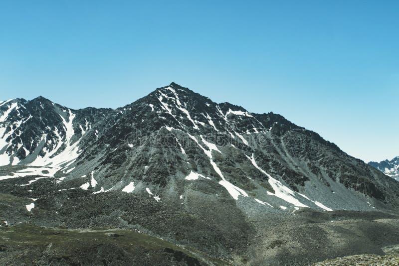 Χιονοσκεπή βουνά, ένας ουρανός με τα σύννεφα σε νότιο φωτογραφία που τονίζετα&i στοκ φωτογραφίες