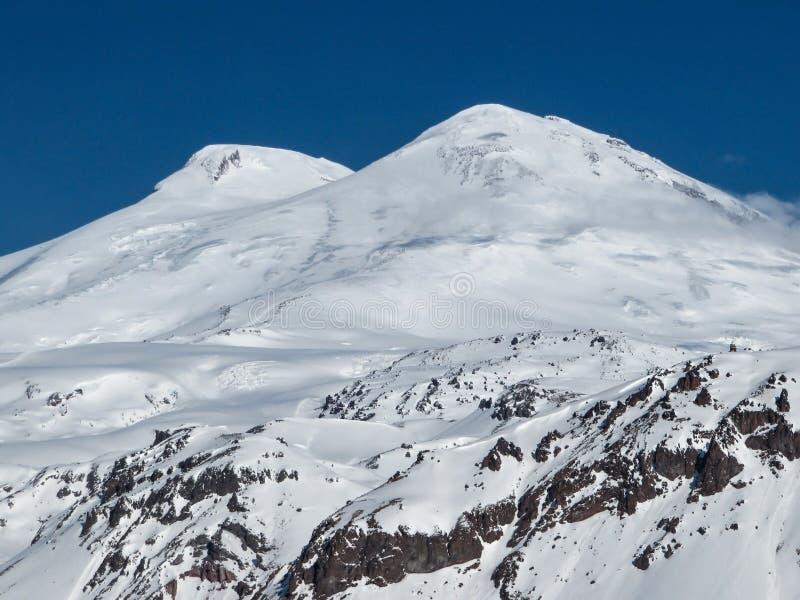 Χιονώδεις αιχμές του υποστηρίγματος Elbrus μια φωτεινή ασυννέφιαστη ημέρα στοκ εικόνα