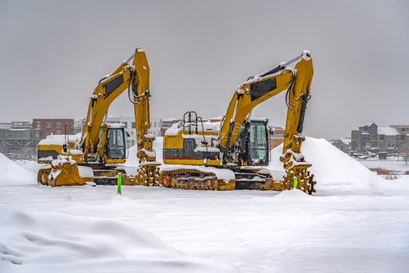 Χιονώδεις εκσκαφείς κατά τη διάρκεια του χειμώνα στη χαραυγή Γιούτα στοκ φωτογραφία