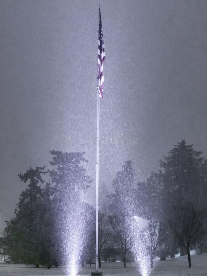 Χιονώδης χειμερινή νύχτα με την αναμμένη επάνω αμερικανική σημαία στοκ εικόνα με δικαίωμα ελεύθερης χρήσης