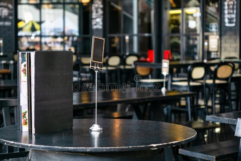Χλεύη επάνω στο κενό πλαίσιο επιλογών κάλυψης στο θολωμένο υπόβαθρο του υπαίθριου πεζουλιού καφέ και εστιατορίων με τους πίνακες  στοκ φωτογραφία