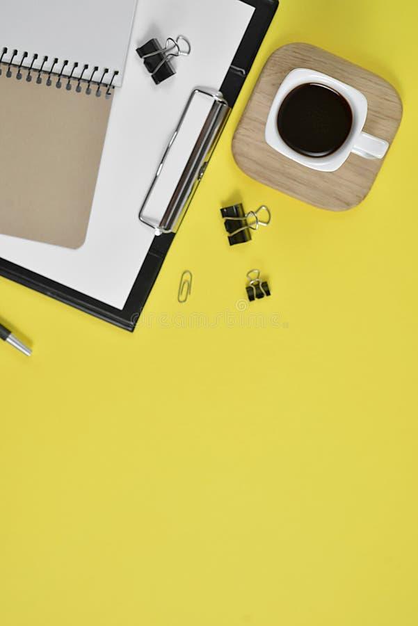 Χλεύη επάνω στο χώρο εργασίας με τον κενό πίνακα συνδετήρων, τις προμήθειες γραφείων, τη μάνδρα, το φλυτζάνι καφέ σε μια ξύλινη σ στοκ εικόνα
