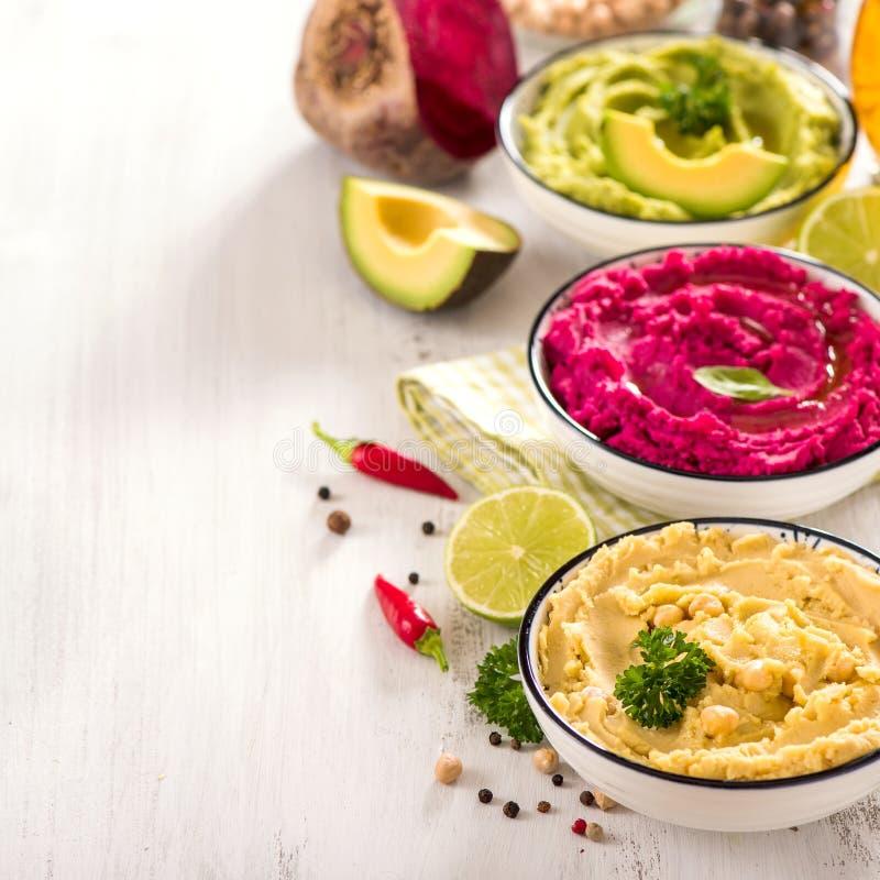 Χορτοφάγο hummus, διαφορετικές εμβυθίσεις, vegan hummus πρόχειρων φαγητών, παντζαριών και αβοκάντο, χορτοφάγος που τρώνε, τετραγω στοκ εικόνες