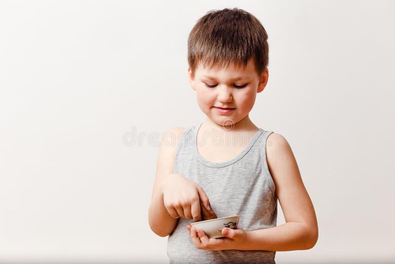5χρονο ευτυχές παιδί σε μια γκρίζα μπλούζα που κρατά μια γλυκά τηγανίτα και ένα μέλι σε ένα άσπρο υπόβαθρο Τηγανίτες μαγείρων στοκ εικόνες