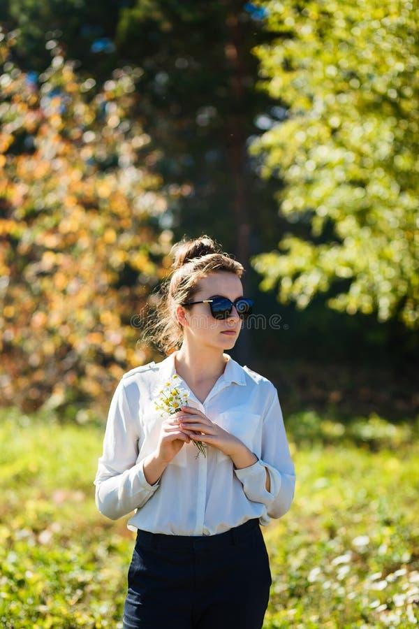 16χρονο κορίτσι στα γυαλιά ηλίου και ένα λευκό πουκάμισο που κρατά μια μικρή ανθοδέσμη των μαργαριτών τομέων το καλοκαίρι στοκ φωτογραφίες με δικαίωμα ελεύθερης χρήσης