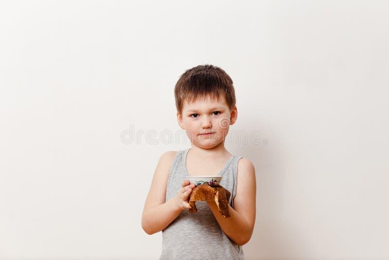 5χρονο παιδί σε μια γκρίζα μπλούζα που κρατά μια γλυκά τηγανίτα και ένα μέλι στοκ εικόνες
