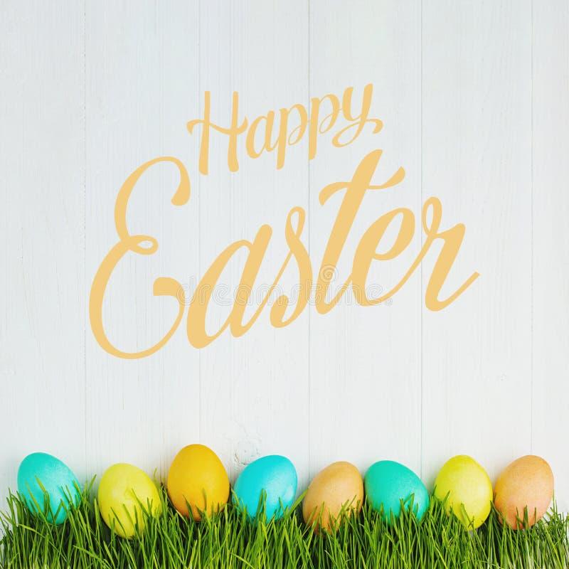 Χρωματισμένα αυγά Πάσχας στη χλόη, σε έναν άσπρο πίνακα, τη τοπ άποψη στοκ εικόνα