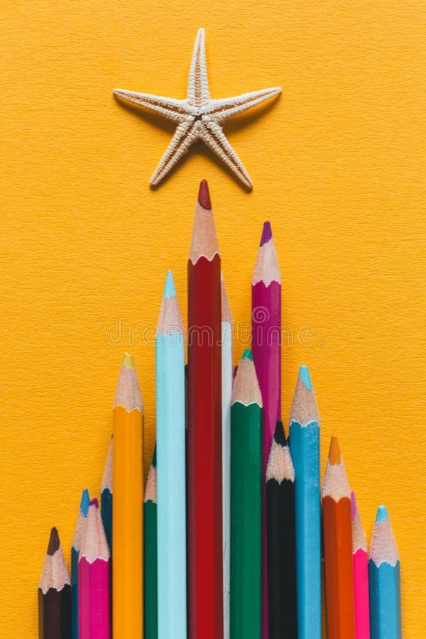 Χρωματισμένα μολύβια που σχεδιάζονται σε μια πυραμίδα Πάνω από τον αστερία μολυβιών Σε ένα κίτρινο υπόβαθρο εγγράφου στοκ φωτογραφίες
