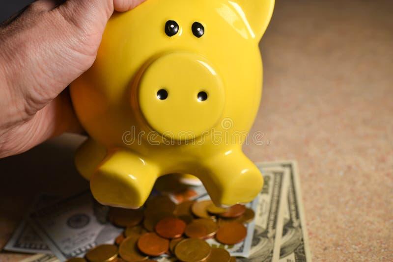 Χύσιμο νομισμάτων από τη piggy τράπεζα χοίρων στοκ εικόνες με δικαίωμα ελεύθερης χρήσης