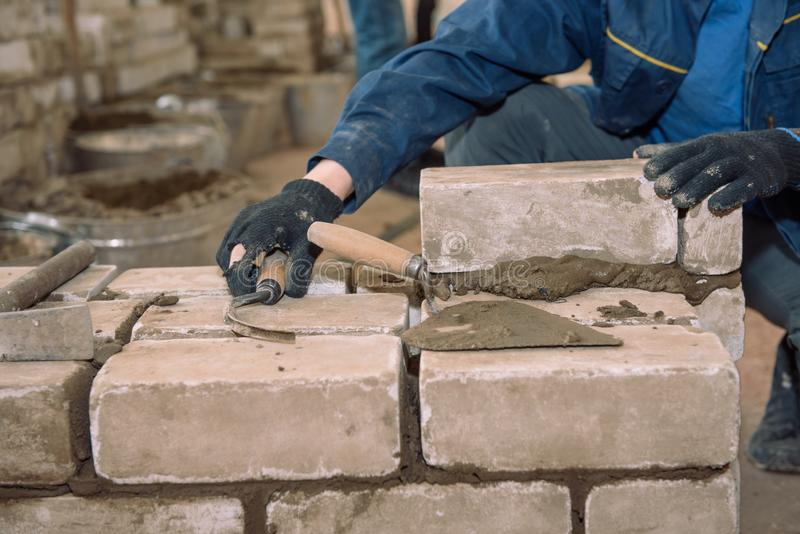 Χτίστε έναν τοίχο των τούβλων Οι σπουδαστές μαθαίνουν να βάζουν τα τούβλα Τούβλα δεσμών τσιμέντου Spatula το τσιμέντο Οικοδόμος ε στοκ εικόνα με δικαίωμα ελεύθερης χρήσης