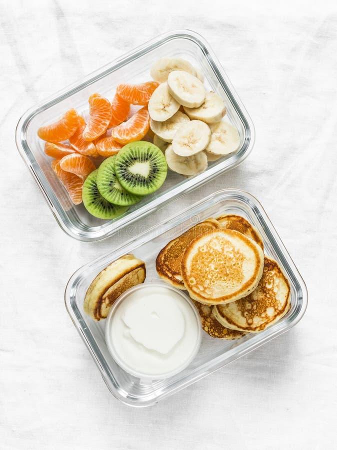 Υγιές σχολικό καλαθάκι με φαγητό παιδιών - τηγανίτες με την ξινές κρέμα και την μπανάνα, ακτινίδιο, tangerine φρούτα Εύγευστο πρό στοκ εικόνα με δικαίωμα ελεύθερης χρήσης