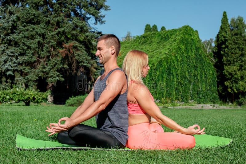 Υγιής τρόπος ζωής Γιόγκα άσκησης ζεύγους που κάθεται υπαίθρια πλάτη με πλάτη χαλιών χαρούμενο στοκ φωτογραφία με δικαίωμα ελεύθερης χρήσης
