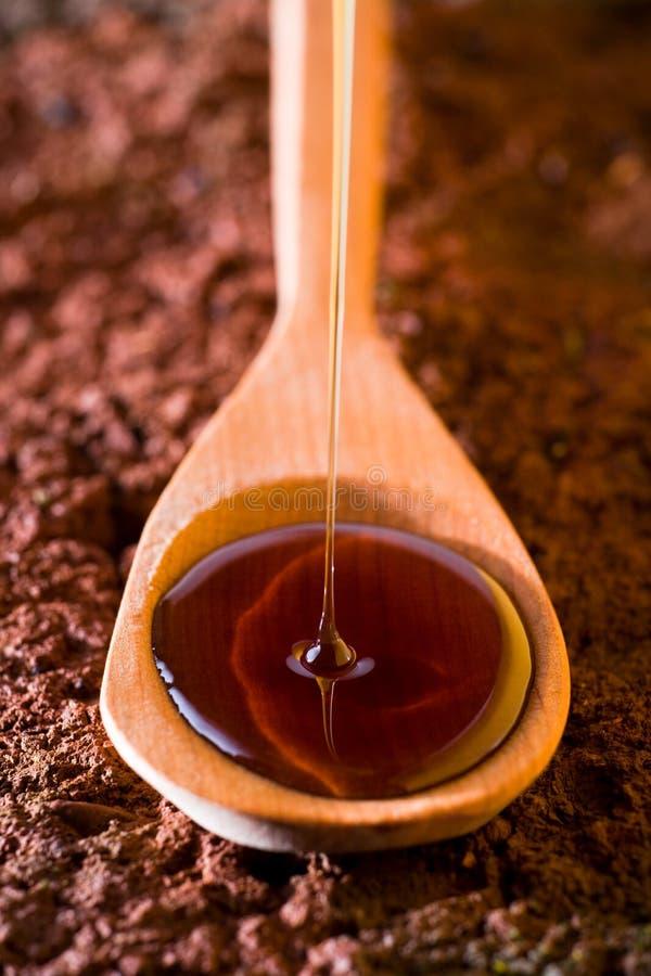 Υγρό μέλι που χύνεται σε ένα κουτάλι στοκ φωτογραφία
