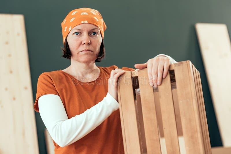 Υπερήφανη θηλυκή τοποθέτηση ξυλουργών με το τελειωμένο ξύλινο κλουβί στοκ φωτογραφία