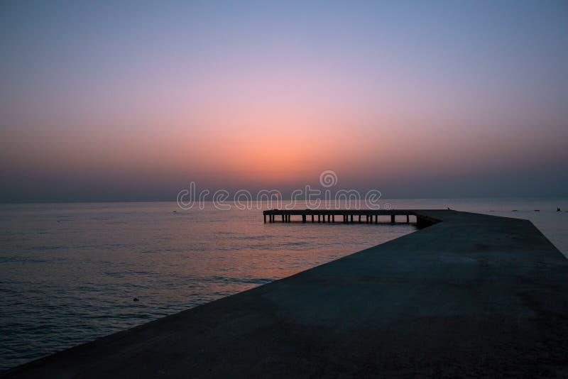 Υπόβαθρο με την παλαιά ξύλινη αποβάθρα στη θάλασσα στο ηλιοβασίλεμα Ο ήλιος πηγαίνει κάτω στο νερό στοκ φωτογραφίες με δικαίωμα ελεύθερης χρήσης