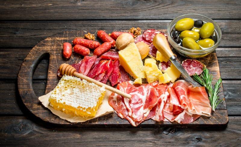 Υπόβαθρο Antipasto Κατάταξη των πρόχειρων φαγητών κρέατος στην επιτροπή με τις ελιές και την παρμεζάνα στοκ εικόνες