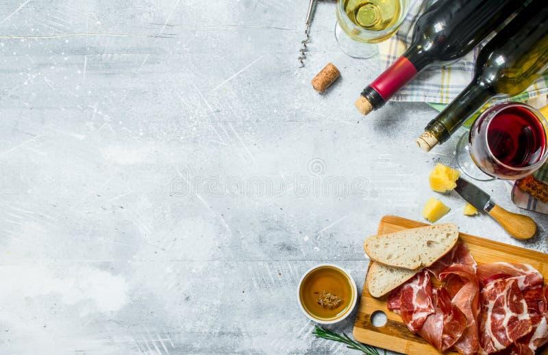 Υπόβαθρο Antipasto Κόκκινο και άσπρο κρασί με τα ορεκτικά κρέατος και τυριών στοκ εικόνα