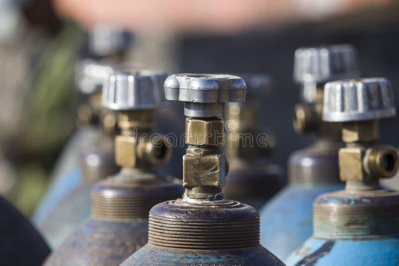 Υπόλοιπος κόσμος των υγροποιημένων εμπορευματοκιβωτίων αερίου οξυγόνου βιομηχανικών με τις βαλβίδες Κλείστε επάνω των βαλβίδων στοκ εικόνες