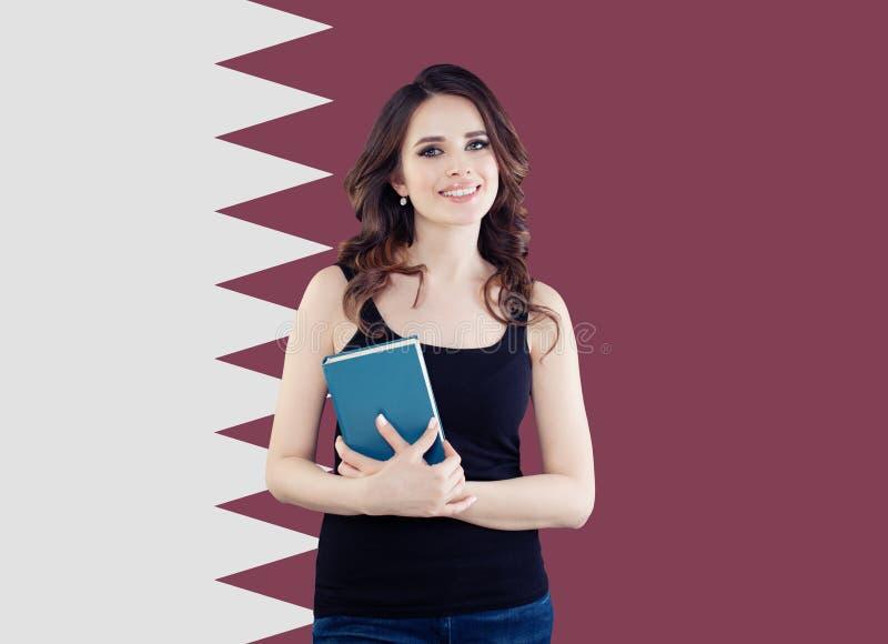 Πάλη για τα δικαιώματα των γυναικών και εκπαίδευση στο Κατάρ Ευτυχής σπουδαστής γυναικών στο κλίμα σημαιών του Κατάρ στοκ φωτογραφία