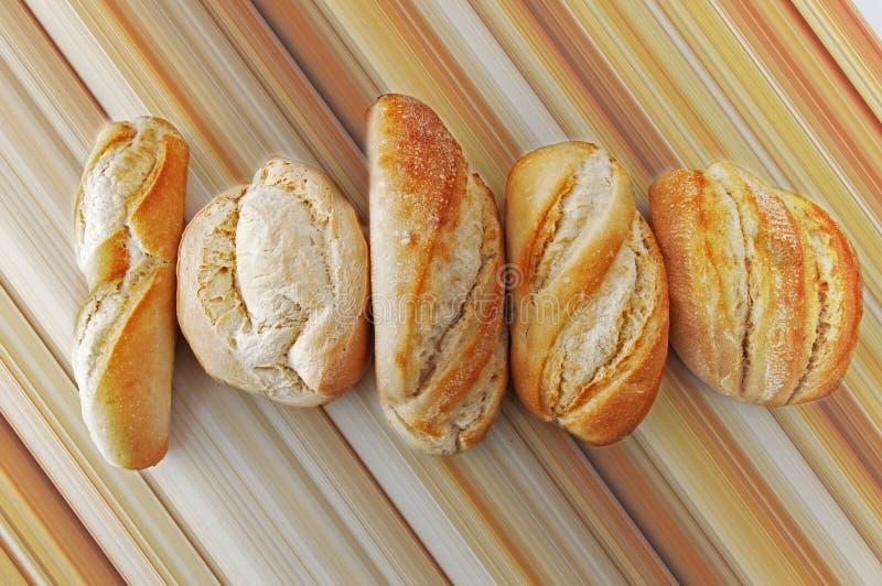 Πέντε διαφορετικά μικρά ψωμιά στο καφετί γραμμικό υπόβαθρο στοκ εικόνες