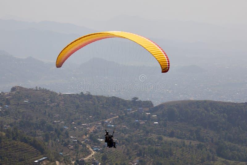 Πέταγμα σε ένα ανεμόπτερο Όμορφη άποψη με τα βουνά και τα ζωηρόχρωμα ανεμόπτερα Ακραίο ταξίδι διακοπών στοκ εικόνα