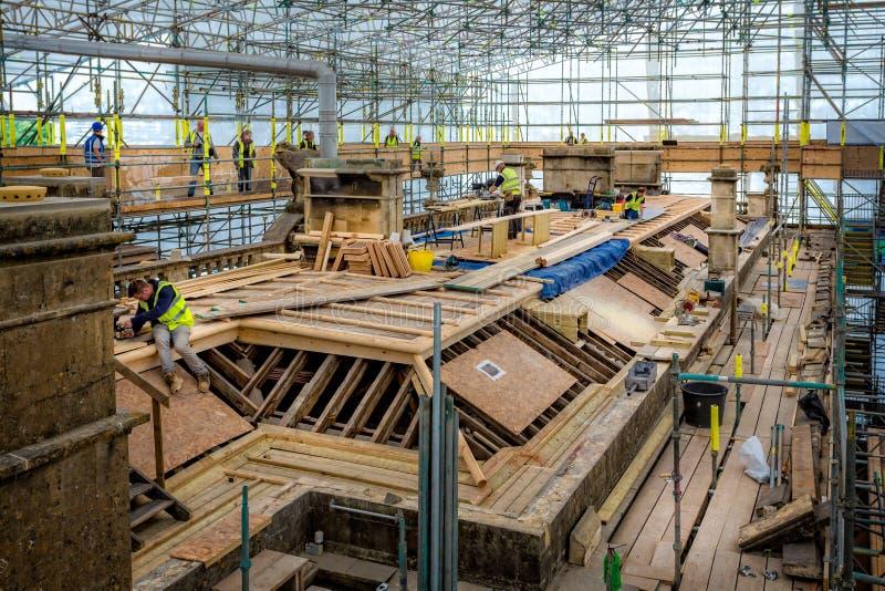 Πέτρινοι κτίστες και roofesr στην εργασία για σημαντικές επισκευές στεγών στο ιστορικό μέγαρο χωρών στο πάρκο Dyrham, Gloucesters στοκ εικόνες