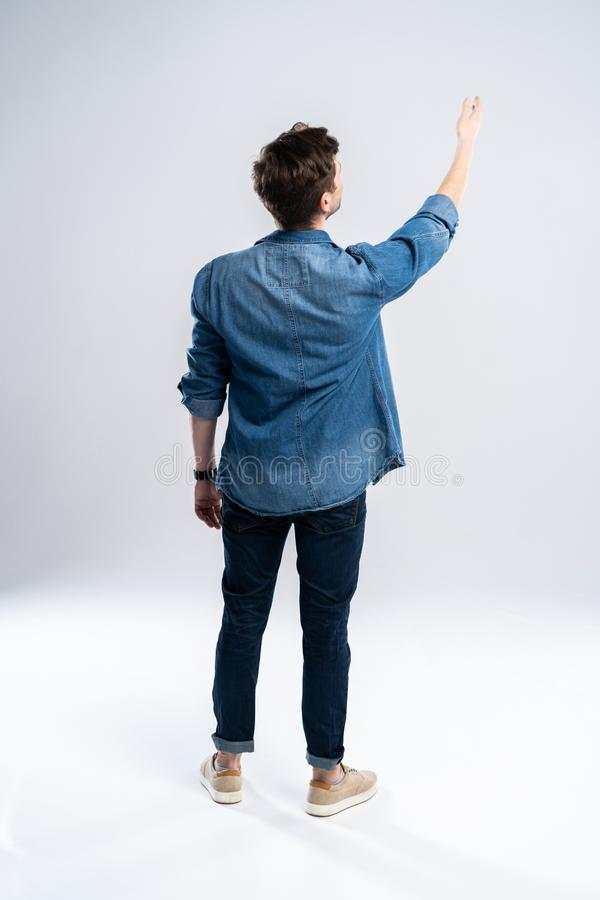 Πίσω άποψη ενός περιστασιακού ατόμου που στέκεται στο άσπρο υπόβαθρο στοκ φωτογραφίες με δικαίωμα ελεύθερης χρήσης