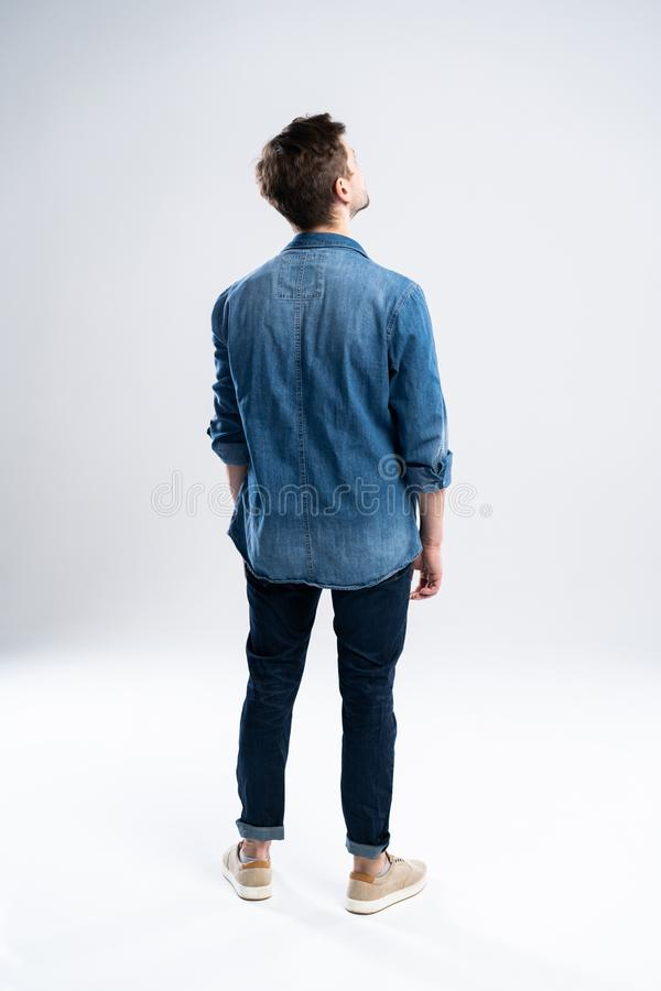 Πίσω άποψη ενός περιστασιακού ατόμου που στέκεται στο άσπρο υπόβαθρο στοκ εικόνα