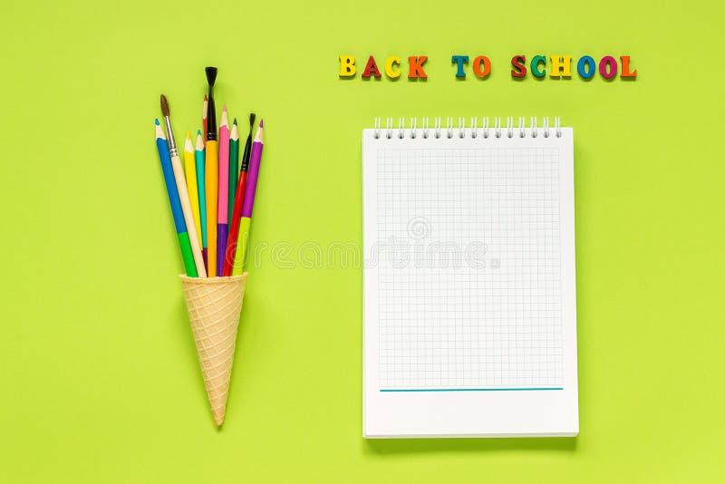 Πίσω στο σχολείο και το χρωματισμένο πινέλο μολυβιών στον κώνο παγωτού βαφλών και το σημειωματάριο στο πράσινο υπόβαθρο Εκπαίδευσ στοκ φωτογραφία με δικαίωμα ελεύθερης χρήσης