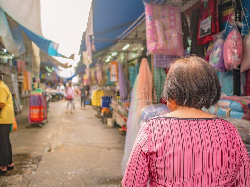 Πίσω των ανώτερων ασιατικών γυναικών που περπατούν και που ψωνίζουν επάνω & x22 Phahurat & x22  Δρόμος η παλαιά αγορά στην πόλη τ στοκ φωτογραφία