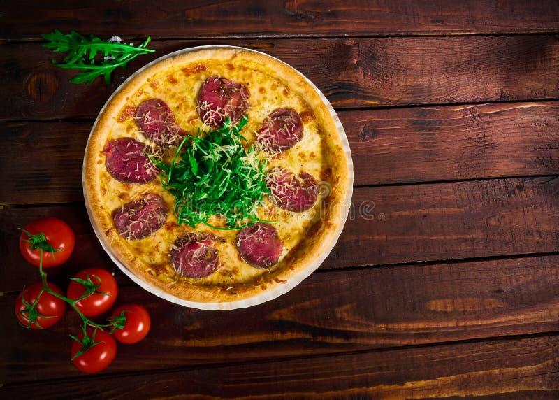Πίτσα με το βόειο κρέας σε έναν ξύλινο πίνακα Όμορφη ανασκόπηση στοκ εικόνα