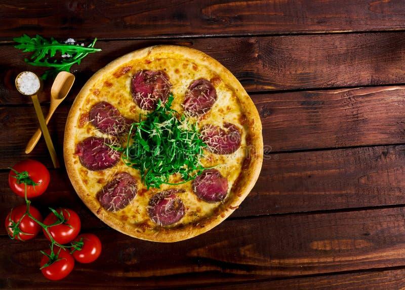 Πίτσα με το βόειο κρέας σε έναν ξύλινο πίνακα Όμορφη ανασκόπηση στοκ φωτογραφίες