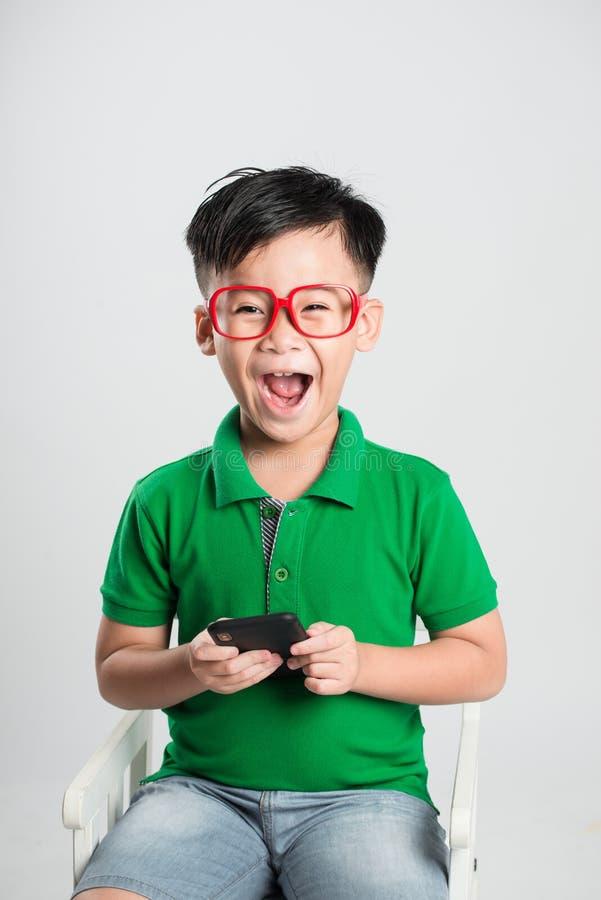 Παίζοντας παιχνίδια λίγων χαμόγελου αγοριών παιδιών ή κάνοντας σερφ Διαδίκτυο στον ψηφιακό υπολογιστή smartphone στοκ εικόνα