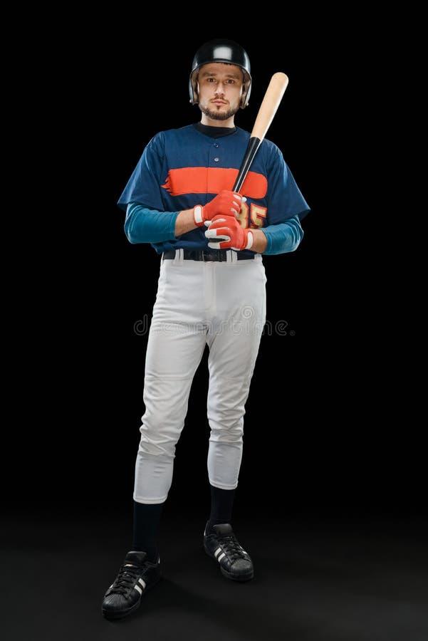 Παίχτης του μπέιζμπολ που κρατά ένα ρόπαλο στοκ εικόνα
