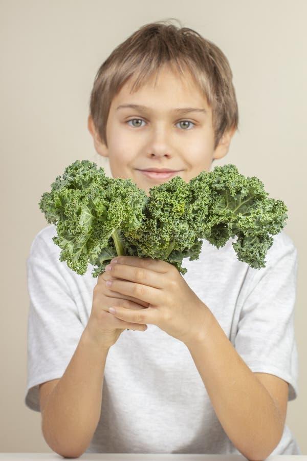Παιδί με τα υγιή λαχανικά Αγόρι που κρατά τα φρέσκα φύλλα κατσαρού λάχανου στοκ φωτογραφίες