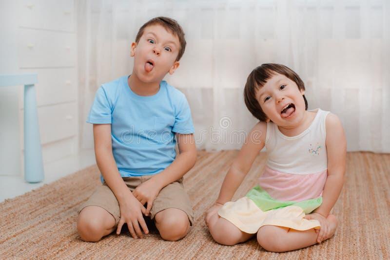 Παιδιά, κορίτσι αγοριών, άτακτο δωμάτιο πατωμάτων μορφάζουν γέλιο _ Τα παιδιά φοβερίζουν τη διασκέδαση των άτακτων παιδιών πλακατ στοκ φωτογραφίες