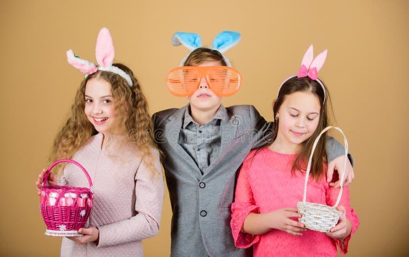 Παιδιά με λίγο έτοιμο κυνήγι καλαθιών για τα αυγά Πάσχας Έτοιμος για το κυνήγι αυγών Εξάρτημα αυτιών λαγουδάκι παιδιών ομάδας στοκ εικόνα