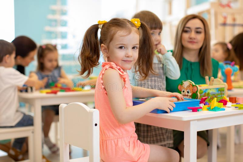 Παιχνίδια δασκάλων με τα παιδιά στον παιδικό σταθμό στοκ φωτογραφία