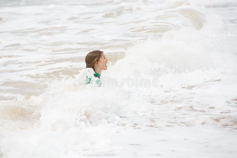 Παιχνίδι κοριτσιών στα κύματα, που έχουν τη διασκέδαση, ντυμένη στο προστατευτικό wetsuit στοκ εικόνες