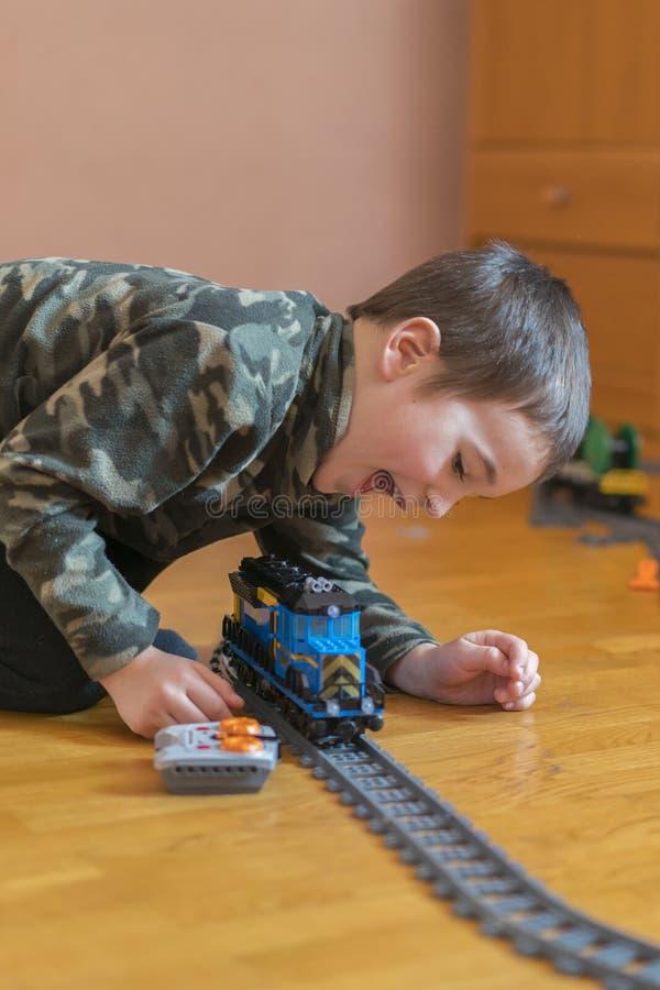 Παιχνίδι μικρών παιδιών με έναν σιδηρόδρομο παιχνιδιών Παιχνίδι μικρών παιδιών με το σιδηρόδρομο που βρίσκεται στο πάτωμα συγκινή στοκ εικόνες με δικαίωμα ελεύθερης χρήσης