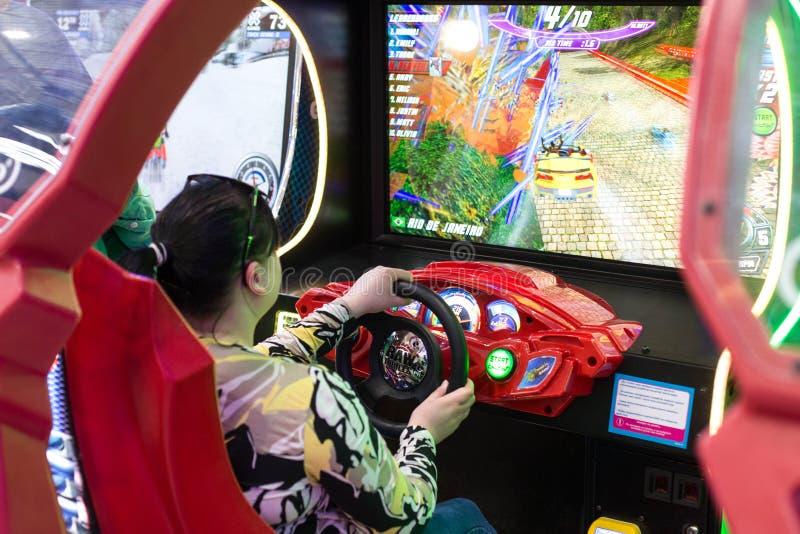 Παιχνίδι παιδιών και ενηλίκων στα μηχανήματα τυχερών παιχνιδιών με κέρματα, έλξη στο εμπορικό κέντρο Οι οικογένειες με τα παιδιά  στοκ εικόνες με δικαίωμα ελεύθερης χρήσης