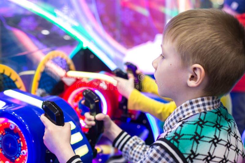 Παιχνίδι παιδιών και ενηλίκων στα μηχανήματα τυχερών παιχνιδιών με κέρματα, έλξη στο εμπορικό κέντρο Οι οικογένειες με τα παιδιά  στοκ φωτογραφίες
