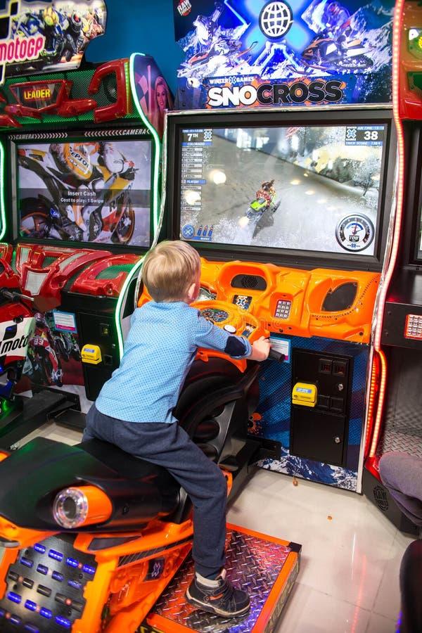 Παιχνίδι παιδιών και ενηλίκων στα μηχανήματα τυχερών παιχνιδιών με κέρματα, έλξη στο εμπορικό κέντρο Οι οικογένειες με τα παιδιά  στοκ εικόνες