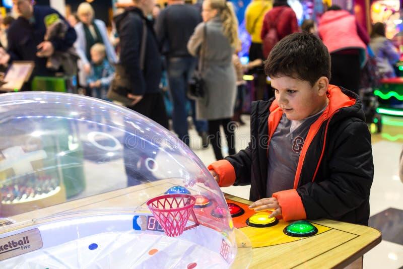 Παιχνίδι παιδιών και ενηλίκων στα μηχανήματα τυχερών παιχνιδιών με κέρματα, έλξη στο εμπορικό κέντρο Οι οικογένειες με τα παιδιά  στοκ εικόνα με δικαίωμα ελεύθερης χρήσης